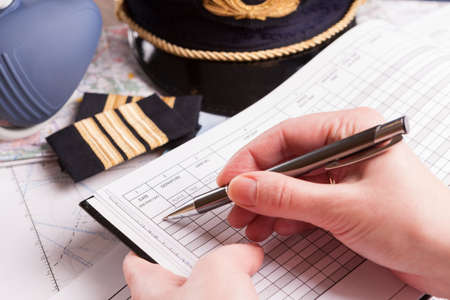 airline pilot: Close up of an airplane pilot hand filling in logbook with equipment including hat, epaulettes and other documents in background Stock Photo