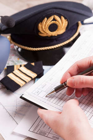 filling in: Close up of an airplane pilot hand filling in logbook with equipment including hat, epaulettes and other documents in background Stock Photo