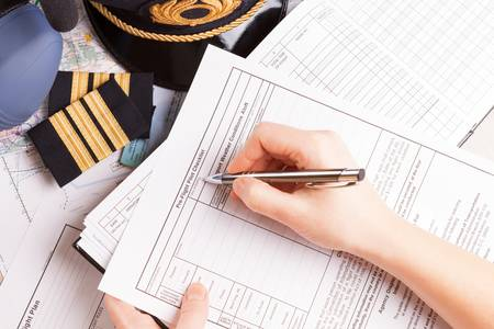 epaulettes: Close up of an airplane pilot hand filling in an flight plan with equipment including hat, epaulettes and other documents in background Stock Photo