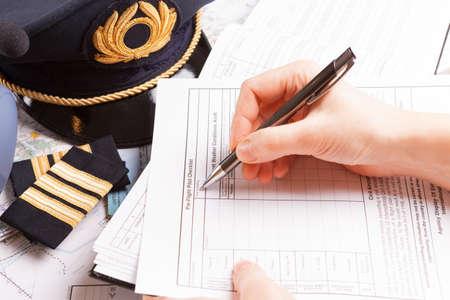 Nahaufnahme von einem Flugzeug Pilot Hand Ausfüllen eines Flugplans mit Ausrüstung einschließlich Hut, Schulterklappen und andere Dokumente im Hintergrund Standard-Bild