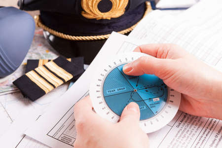 epaulettes: Close up of an airplane pilot hands with holding pattern calculator with equipment including hat, epaulettes and other documents in background