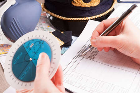 epaulettes: Close up of an airplane pilot hand with holding pattern calculator filling in an flight plan and with equipment including hat, epaulettes and other documents in background