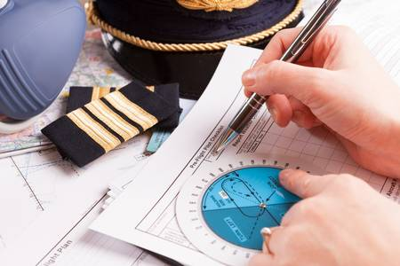 Close up of an airplane pilot hand filling in an flight plan with equipment including hat, epaulettes and other documents in background Stock Photo - 18145668