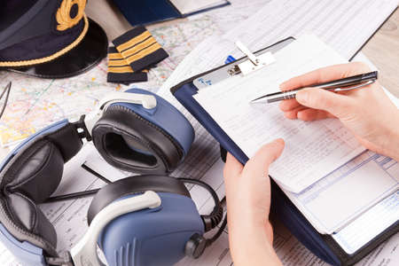 epaulettes: Close up of an airplane pilot hand filling in an pre-fligh checklist and holding weather forecast with equipment including hat, epaulettes and other documents in background