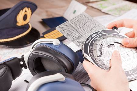 Close up of an airplane pilot hand holding flight computer and making pre-flight calculations with equipment including hat, epaulettes and other documents in background Stock Photo