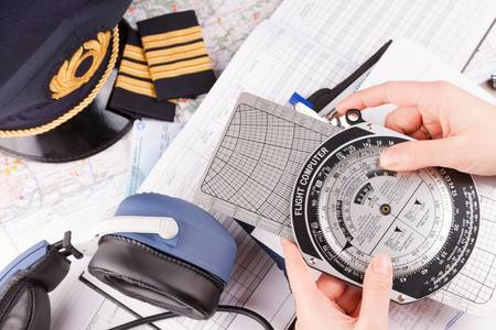 accesories: Close up of an airplane pilot hand holding flight computer and making pre-flight calculations with equipment including hat, epaulettes and other documents in background Stock Photo