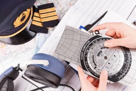 piloto de avion: Primer plano de una mano sosteniendo piloto de avión computadora de vuelo y hacer cálculos previos al vuelo con el equipo, incluyendo sombrero, hombreras y otros documentos de antecedentes Foto de archivo