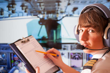 piloto: Piloto mujer hermosa que desgasta el uniforme con epauletes y auriculares, escribiendo en bloc de notas dentro de avión Foto de archivo