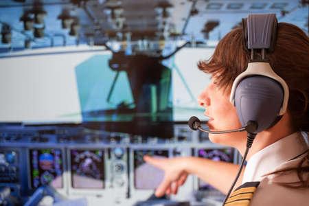 piloto de avion: Piloto mujer hermosa que desgasta el uniforme con epauletes y auriculares sentado en el interior de avión y apuntando a la cabina durante el vuelo