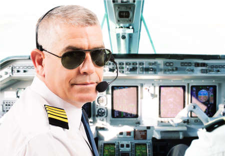 epaulettes: Airline pilot wearing uniform with epaulettes and headset working in airliner during flight