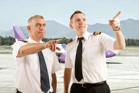 airstrip: Cheerful two airline pilots wearing uniform with epaulettes standing on airstrip and pointing at something with airplane in the background Stock Photo