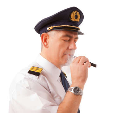 Airline pilot wearing uniform with epaulettes and hat smoking electronic cigarette, isolated on white  photo