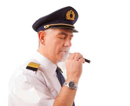 cigarrillos: Piloto de L�nea A�rea llevaba uniforme con charreteras y sombrero de cigarrillos cigarrillo electr�nico, aislado en blanco