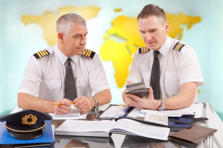 co work: Two airline pilots preparing to flight, checking calculator, papers, flight plan, log book  Pilots are sitting in AIS ARO Air Traffic Services Reporting Office Stock Photo