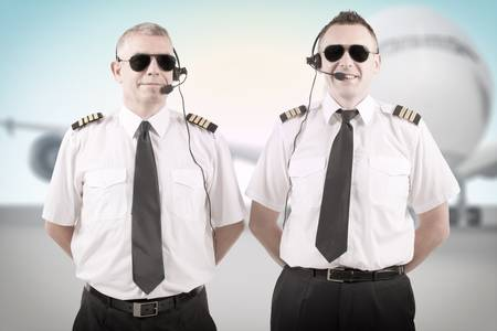cpl: Cheerful airline pilots wearing uniforms with epauletes and headsets standing with airliner in background   Stock Photo