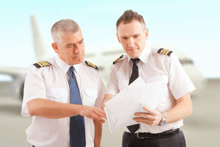 airline pilot: Airline pilots wearing uniform with epaulettes checking papers, passenger aircraft in background Stock Photo