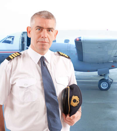 Airline pilot wearing uniform with epaulettes with passenger aircraft in background photo