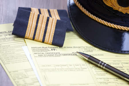 Close up of an airplane pilot equipment hat and epaluetes with medical forms and pen. Conceptual image of medical exam. Stock Photo - 18246870