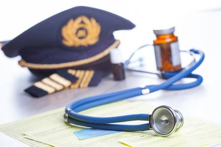 Close up of an airplane pilot equipment hat and epaluetes with doctor's stethoscope, forms, medical and pilot certificate and drugs. Conceptual image of medical exam. Stock Photo - 18246847