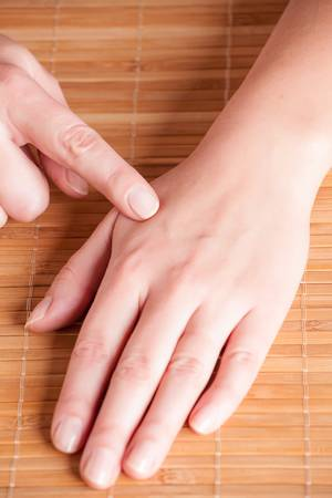 acupressure: Acupressure, acupuncture point Hegu, LI4. Photo shows how to find this point. Stock Photo
