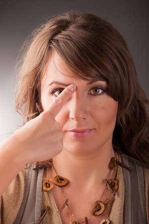 tapping: Donna che fa EFT sulla fine del punto sopracciglio Emotional Freedom Techniques, toccando, una forma di intervento di consulenza che attinge varie teorie della medicina alternativa