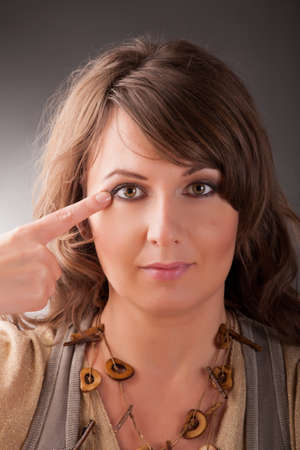 meridians: Woman doing EFT on the corner of the eye point  Emotional Freedom Techniques, tapping, a form of counseling intervention that draws on various theories of alternative medicine