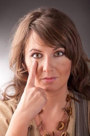 tapping: Donna facendo EFT sul punto sotto gli occhi Emotional Freedom Techniques, toccando, una forma di intervento consulenza che attinge a varie teorie della medicina alternativa