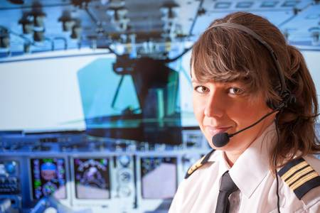 airline uniform: Beautiful woman pilot wearing uniform with epauletes, headset sitting inside airliner with visible cockpit during flight  Stock Photo