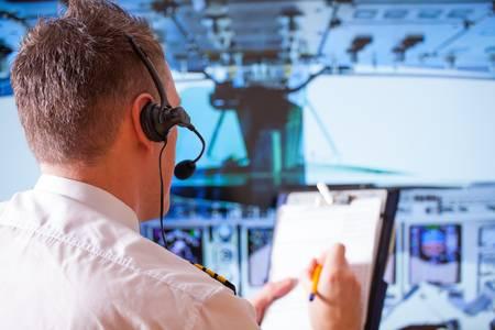 piloto: Piloto de avión llevaba uniforme con epauletes y auriculares, escribiendo en el bloc de notas dentro de avión