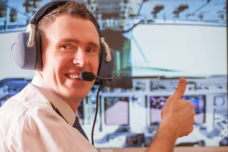 Pilot wearing uniform with epauletes, sitting inside airliner, thumb up, with visible cockpit during flight  Stock Photo