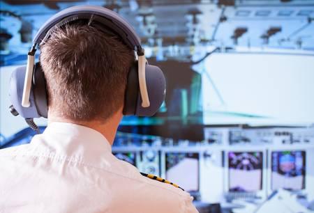 piloto: Airline piloto llevaba uniforme con charreteras y los auriculares que trabajan en avión durante el vuelo