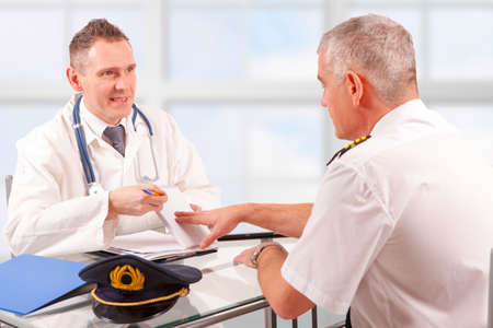 faa: Airplane pilot during medical exam with doctor presenting papers Stock Photo
