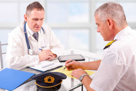 faa: Airplane pilot during medical exam with doctor filling in a form Stock Photo