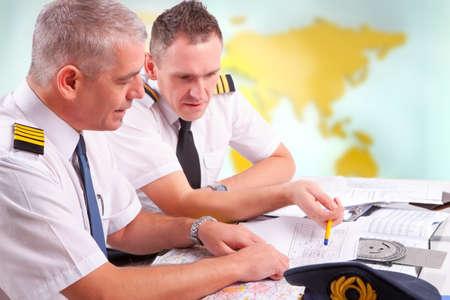 piloto: Dos pilotos de l�neas a�reas prepar�ndose para el vuelo, plan de control de documentos de vuelo, pilotos iniciar libro est� sentado en AIS servicios de tr�nsito a�reo notificante Oficina ARO