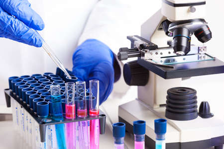 drug discovery: Lab technician working with equipment  tweezers, microscope, test tubes  filled with colored fluid, chemical flasks