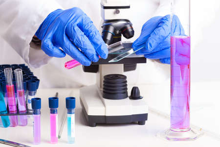 Lab technician working with equipment  tweezers, microscope, test tubes  filled with colored fluid, chemical flasks photo