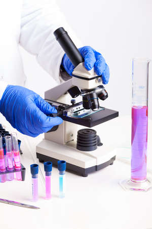 Lab technician working with equipment  tweezers, microscope, test tubes  filled with colored fluid, chemical flasks Stock Photo - 19061323