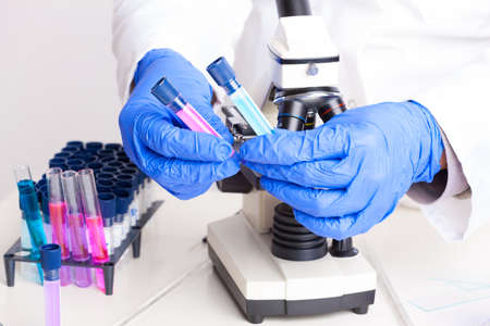 Lab technician working with equipment  tweezers, microscope, test tubes  filled with colored fluid, chemical flasks