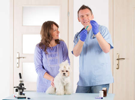 Smiling veterinian preparing vaccination, standing with his client and her dog maltese photo