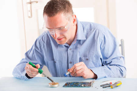 soldered: Man using soldering tool for the computer parts. Stock Photo