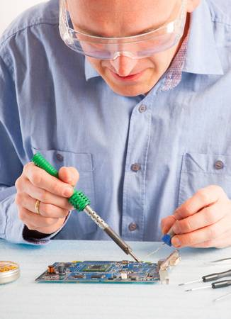 Man using soldering tool for the computer parts. photo
