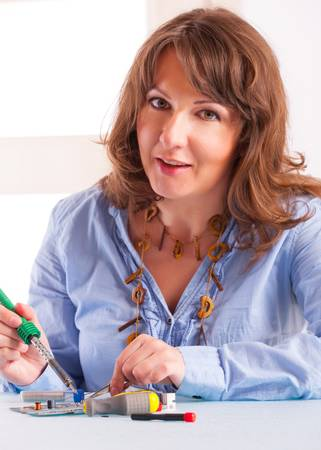 Woman using soldering tool for the computer parts. photo
