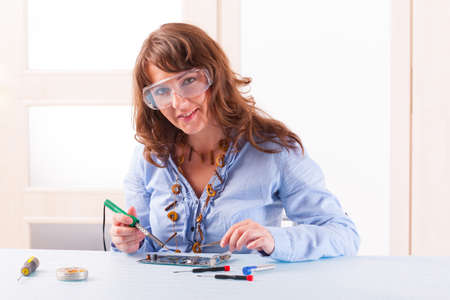 soldered: Beautiful woman in protective glasses fixing computer parts with and soldering iron and other tools