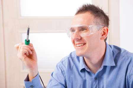 soldered: Man using soldering tool wearing safety glasses