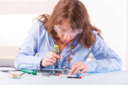 soldered: Beautiful woman in protective glasses fixing computer parts with screwdriver and soldering iron