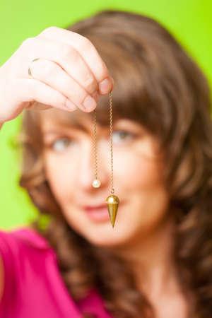 pendulum: Beautiful woman with pendulum in her hand, tool for dowsing  Stock Photo