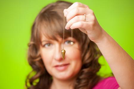 hypnotist: Beautiful woman with pendulum in her hand, tool for dowsing  Stock Photo
