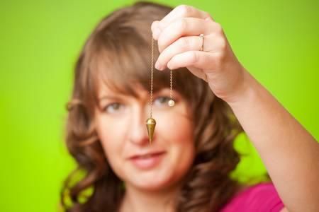 pr�voyance: Belle femme avec pendule dans sa main, outil de radiesth�sie