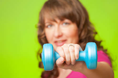 Woman doing exercise with dumb bell, strengthen her arms and shoulders photo