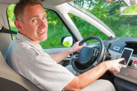 gps navigation: Happy man in the car using his mobile as a navigation GPS or receiving call Stock Photo